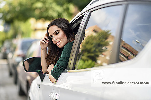 Young woman leaning out the window of her car in the city