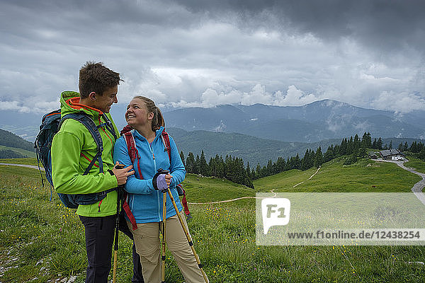 Germany  Lenggries  happy young couple with hiking poles and backpacks on Alpine meadow