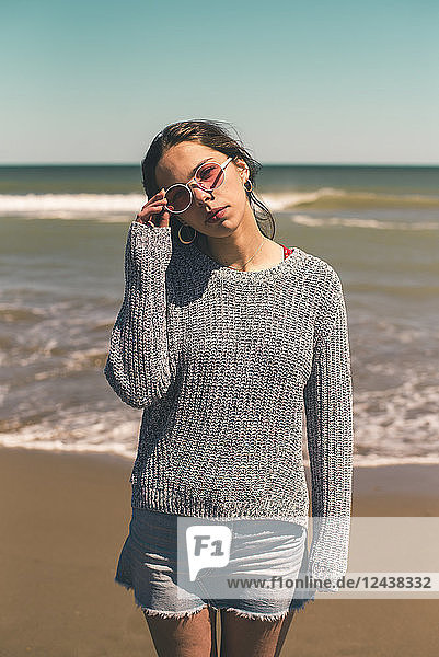 Spain  portrait of young woman wearing sunglasses standing on the beach