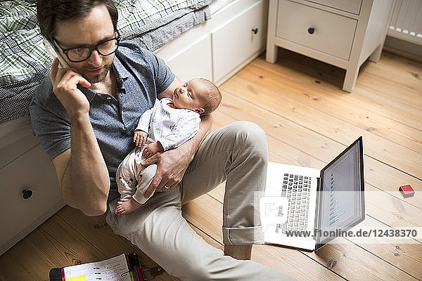 Father with his baby daughter working from home