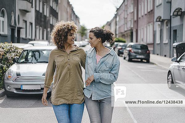 Best friends walking in the city  arm in arm