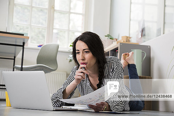 Casual woman with sheet of paper and laptop lying on the floor in office