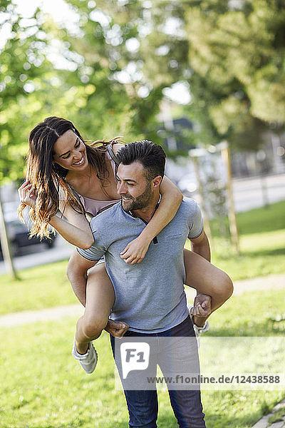 Happy man giving girlfriend a piggyback ride in park