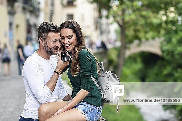 Happy tourist couple using cell phone in the city