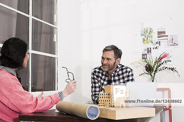 Smiling colleagues sitting at table in an architect's office