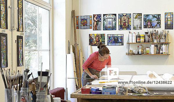 Woman working on draft in glazier's workshop
