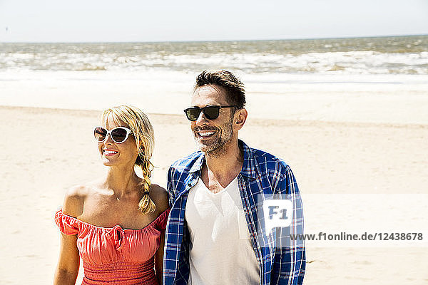 Happy couple wearing sunglasses on the beach