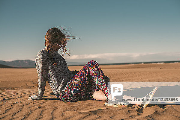 Spain  fashinable young woman sitting on the beach