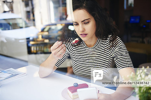 Young woman using cell phone and eating cake at an cafe in the city