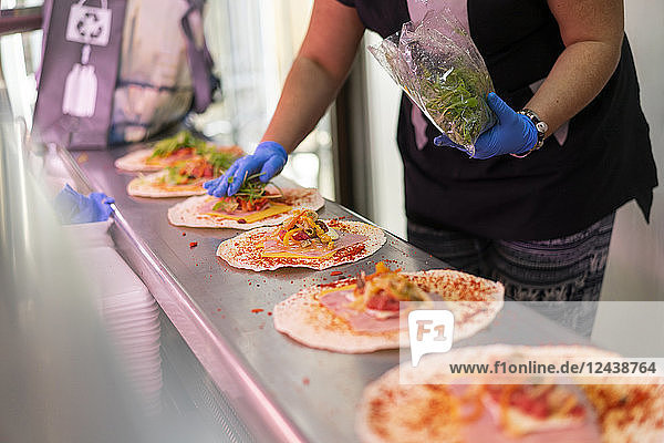 Woman in market stall filling tortilla wraps