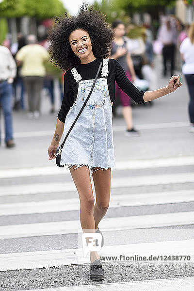 Portrait of happy young woman walking on zebra crossing