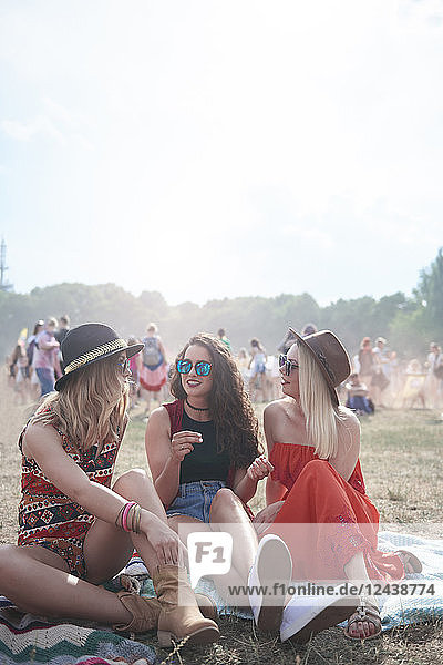 Young people sitting on blanket at music festival