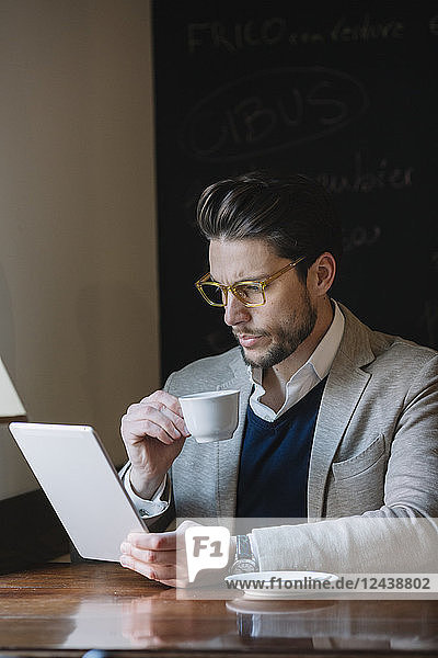 Businessman drinking coffee and using tablet in a cafe