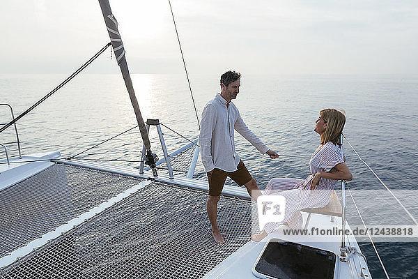 Mature couple standing on catamaran trampoline  enjoying their sailing trip