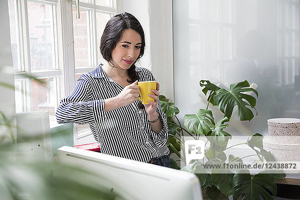Smiling woman with cup of coffee at the window in office