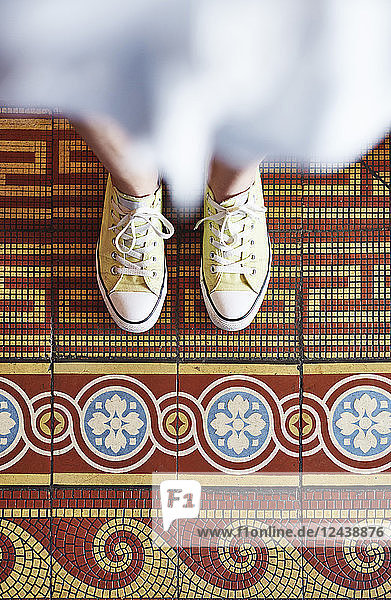 Woman wearing yellow sneakers standing on mosaic floor  partial view