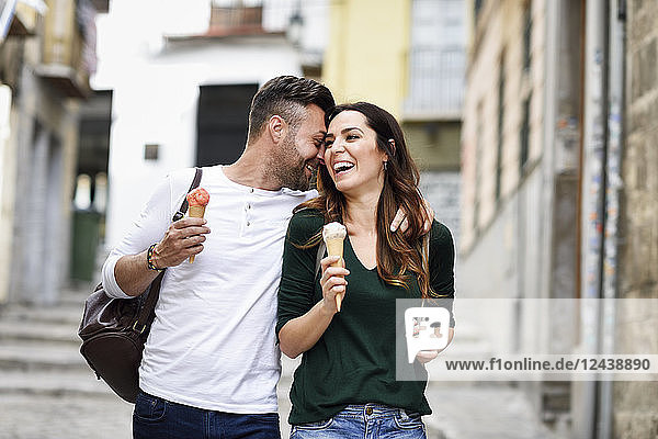 Happy tourist couple with ice cream cones in the city