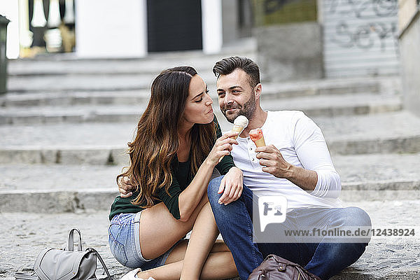 Tourist couple sharing ice cream cones in the city