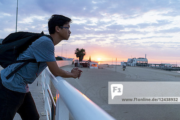 Young Chinese man with backpack looking at beach