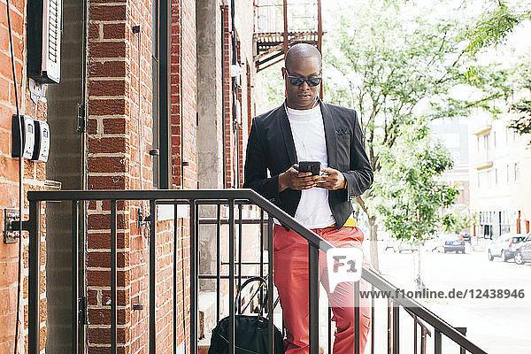 USA  NYC  Brooklyn  Man waiting on stairs  using smartphone