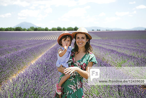 France  Provence  Valensole plateau  portrait of smiling mother and daughter in lavender fields in the summer