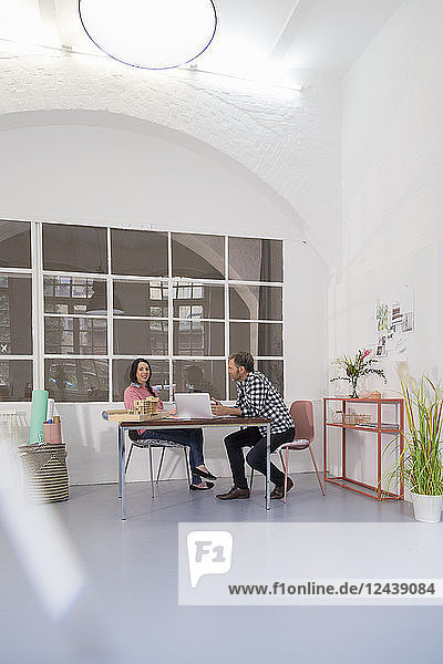 Colleagues sitting at table in an architect's loft office