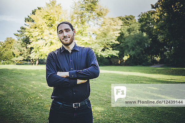 Young businessman standing in park with arms crossed