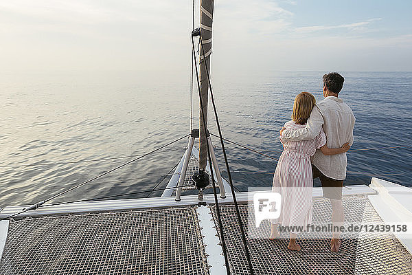 Mature couple standing on catamaran trampoline  enjoying their sailing trip