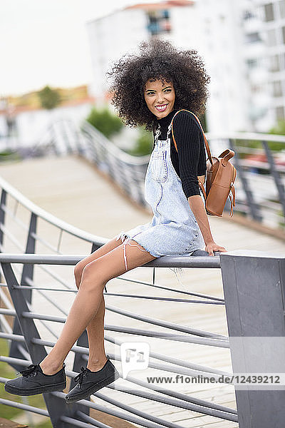 Portrait of smiling young woman with brown leather backpack sitting on railing of a bridge