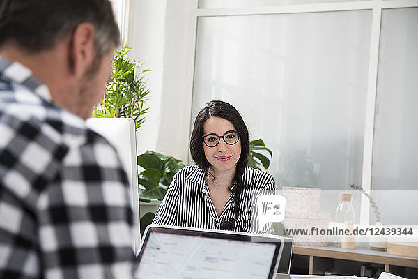 Portrait of smiling woman with colleague working at desk in office