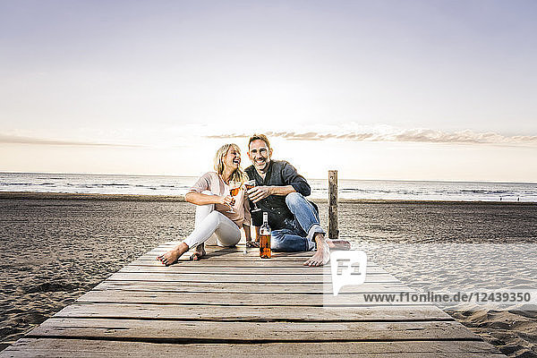 Happy couple with wine glasses sitting on boardwalk on the beach at sunset
