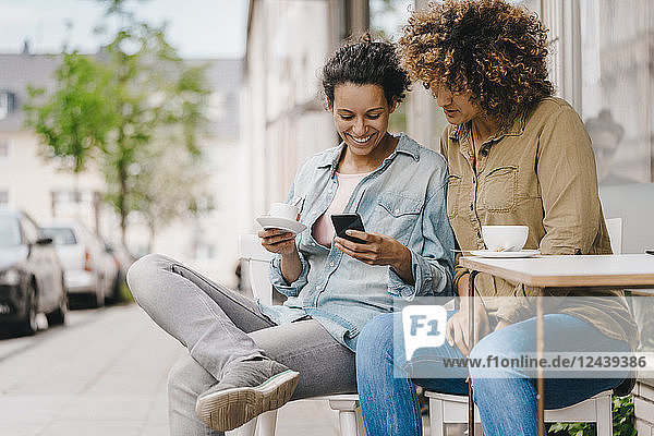 Two friends working in coworking space  sitting at table with coffee  using smartphone
