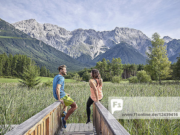 Austria  Tyrol  Mieming  couple resting on a boardwalk in the mountains