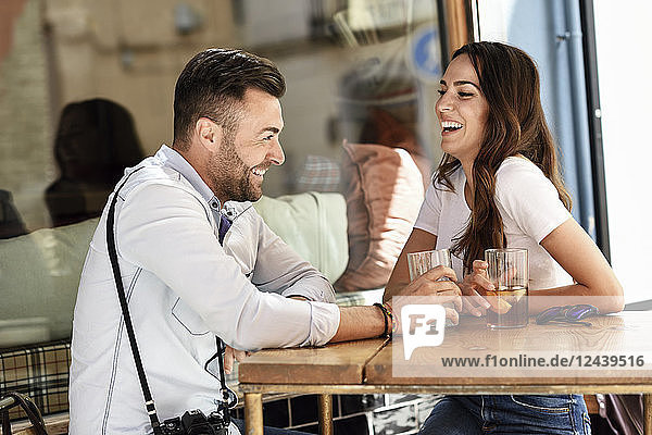 Happy couple having a drink at an outdoor bar in the city