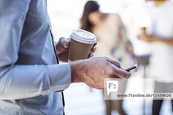 Hand of a man holding cup of coffee  using smartphone