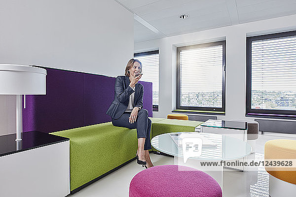 Businesswoman using smartphone in office lounge