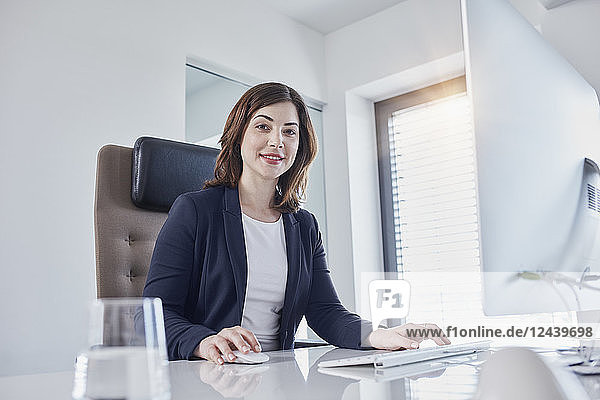Portrait of smiling young businesswoman at desk in office