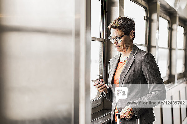 Businesswoman on a ferry looking on cell phone