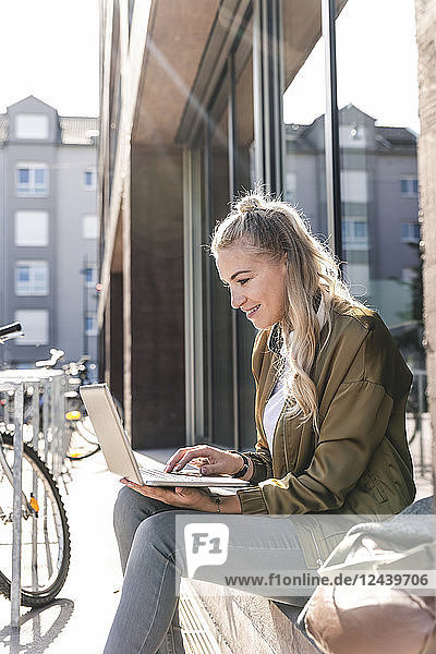 Friends sitting in front of window in the city  using laptop