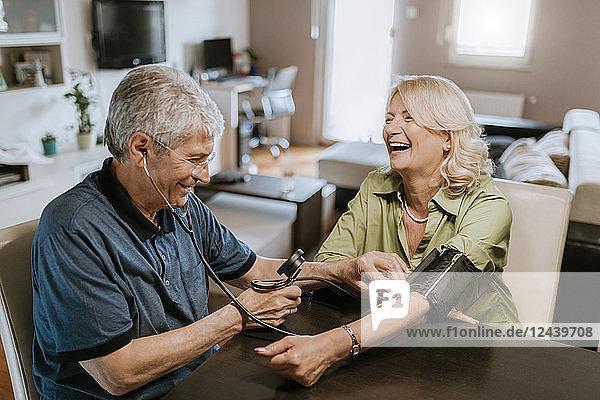 Happy senior couple taking blood pressure