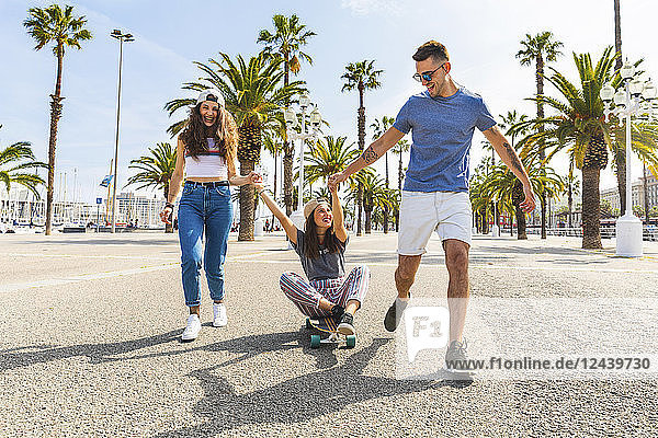 Carefree friends having fun with a skateboard on a promenade with palms