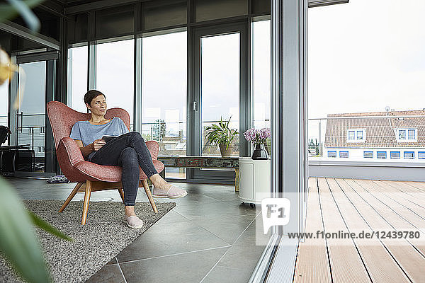 Woman sitting in armchair at home with tablet looking out of balcony door