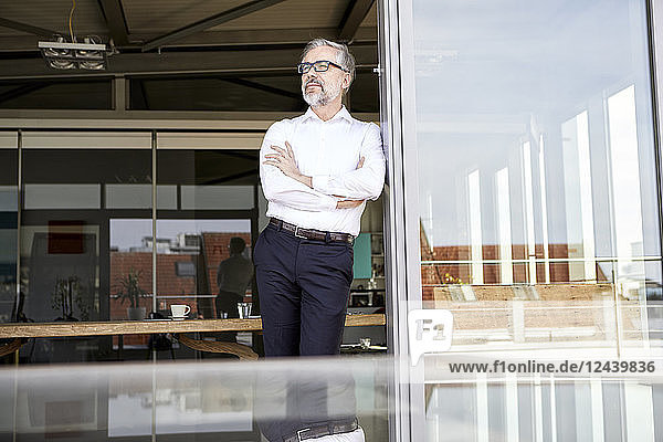 Businessman standing at French door thinking