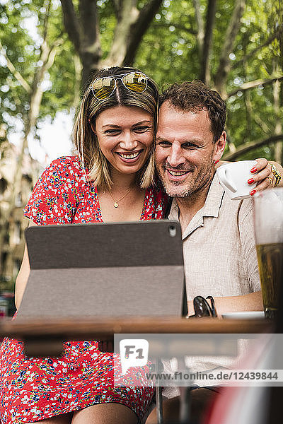Smiling couple sharing tablet at an outdoor cafe