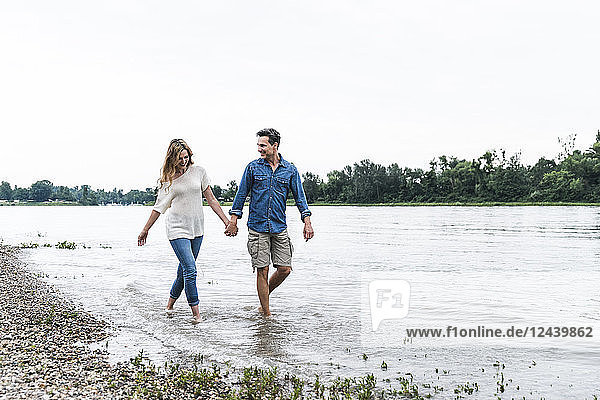 Happy couple wading in river