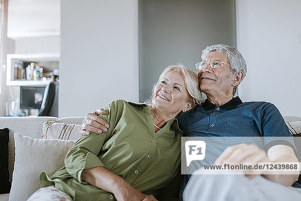 Smiling senior couple sitting on couch at home