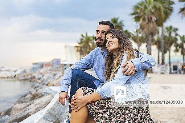 Spain  Barcelona  couple sitting on rocks at the seaside