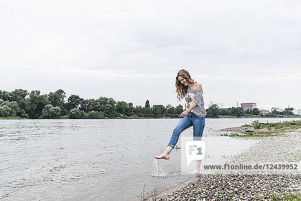 Smiling woman splashing water in a river