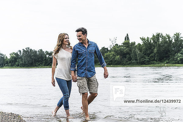 Smiling couple wading in river