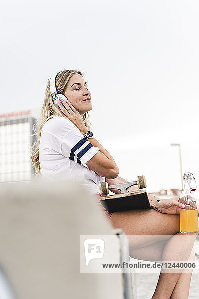 Young woman with skateboard  listening music